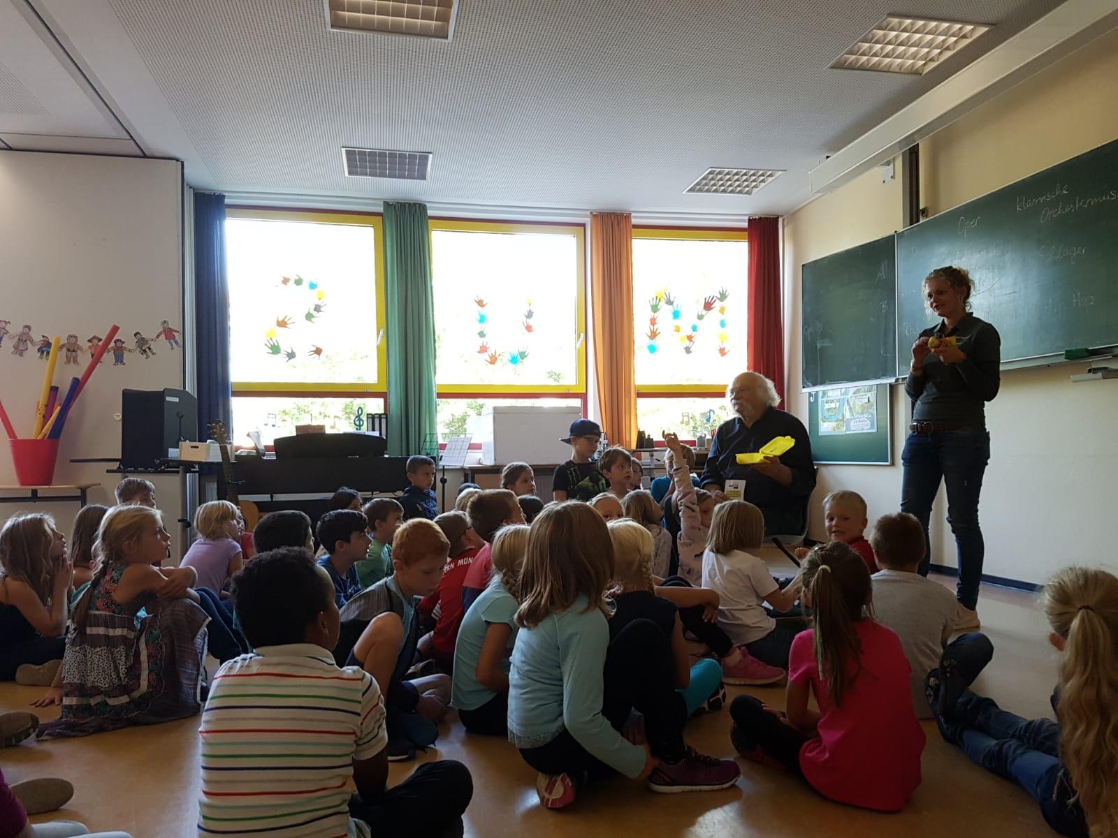 Josef Jacobi und Julia Engemann erklären den Grundschülern den Inhalt der Bio-Brotbox.
