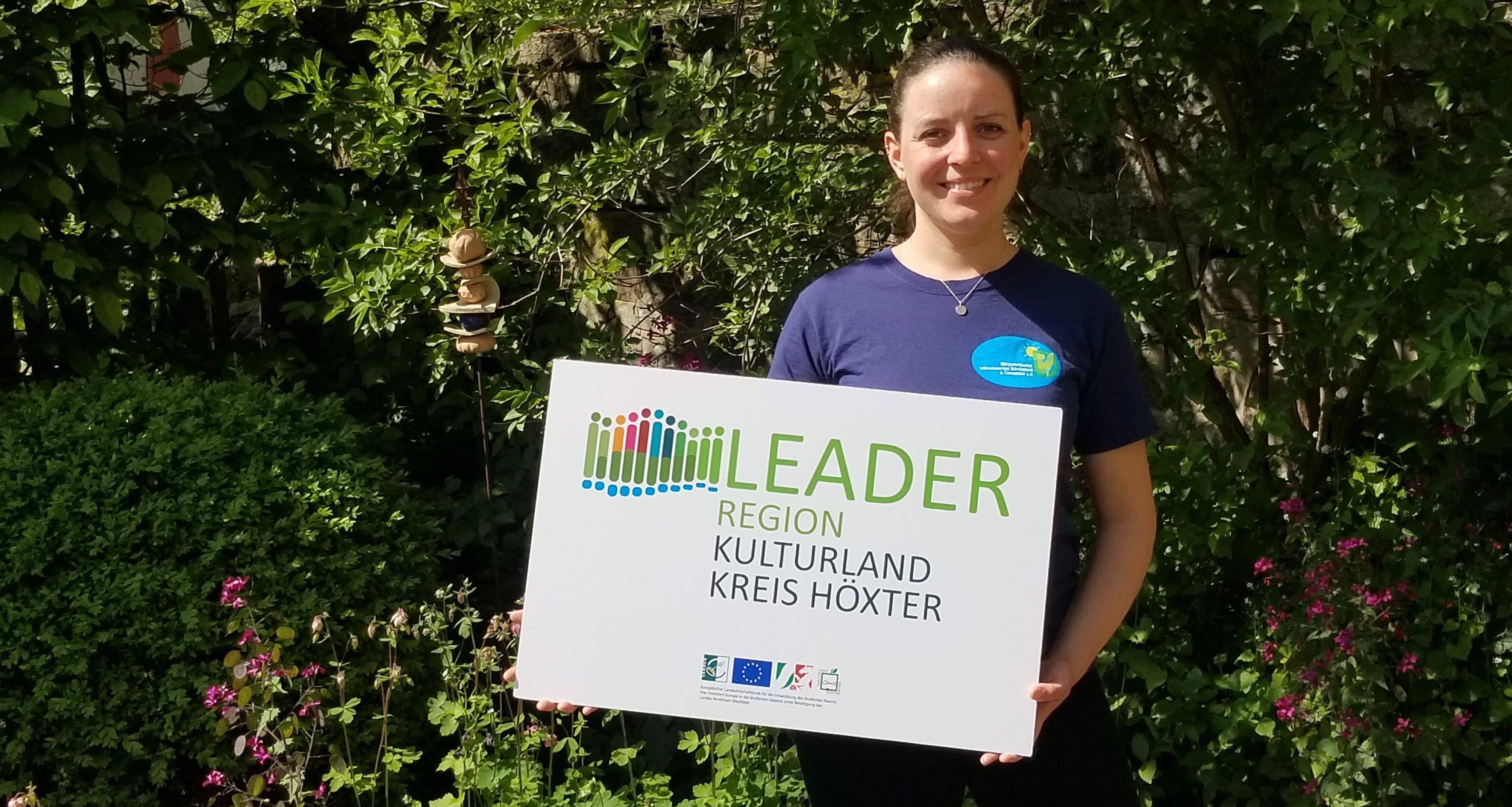 Projektleiterin Vera Prenzel präsentiert das Leader-Schild vor grünen Büschen.